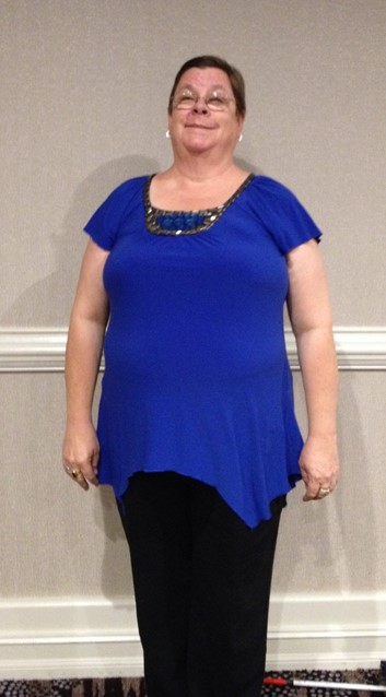 I am pictured wearing a beautiful blue shirt with decorative beading on the front.